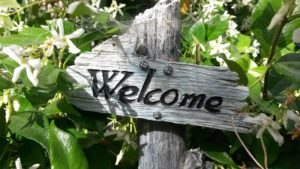 A photograph of a sign, in a garden, that reads Welcome